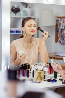 Przyjemna młoda kobieta stojąca przed lustrem podczas nakładania kosmetyków dekoracyjnych