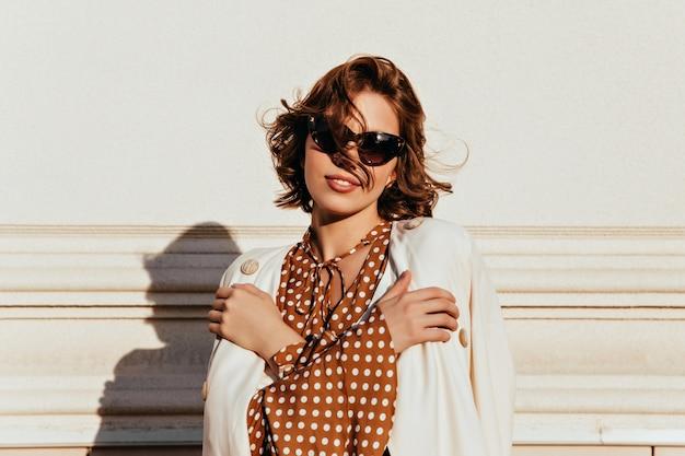 Przyjemna młoda kobieta z brązowymi włosami stoi przed ścianą. odkryty strzał czarującej krótkowłosej modelki w ciemnych okularach.