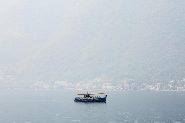 Przyjemna niebieska łódź z żółtą markizą słoneczną na tle wioski i gór we mgle