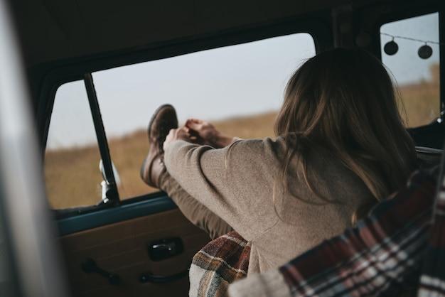 Przyjemna podróż. widok z tyłu młodej kobiety rozciągającej się siedząc na przednim siedzeniu pasażera w samochodzie w stylu retro