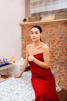 Przyjemna procedura. przystojna naga kobieta okryta czerwonym ręcznikiem podczas wizyty w centrum spa