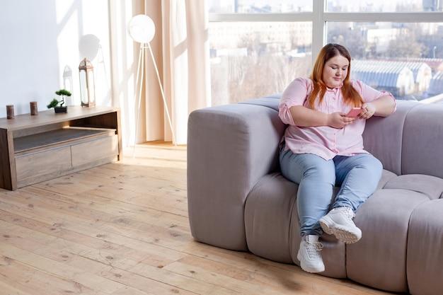 Przyjemna pulchna kobieta patrząca na ekran swojego telefonu podczas korzystania z internetu
