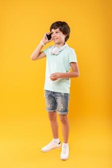 Przyjemna rozmowa. alert ciemnowłosy chłopak uśmiecha się podczas rozmowy przez telefon