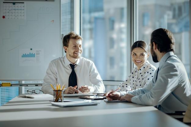 Przyjemna rozmowa. optymistycznie nastawieni młodzi koledzy siedzący przy stole podczas spotkania i radośnie rozmawiający ze sobą, uśmiechając się