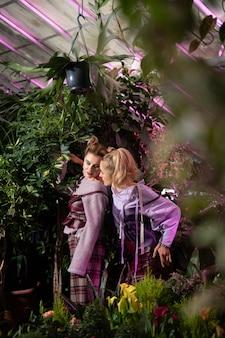 Przyjemna rozmowa. piękne, miłe kobiety rozmawiające ze sobą stojąc w szklarni