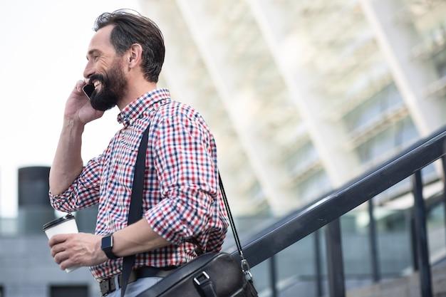 Przyjemna rozmowa. radosny brodaty mężczyzna rozmawia przez telefon podczas spaceru po ulicy