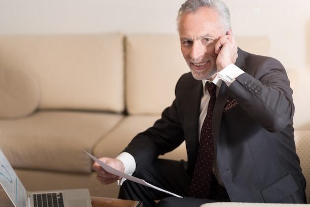 Przyjemna rozmowa. uśmiechnięty wesoły brodaty biznesmen rozmawia przez telefon i siedzi w hotelu przed laptopem, pracując z papierami i wyrażając podekscytowanie
