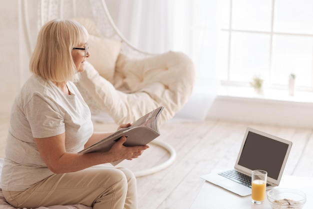 Przyjemna rozrywka. pozytywna radosna starsza kobieta trzymająca magazyn i przewracająca jego strony podczas odpoczynku w domu