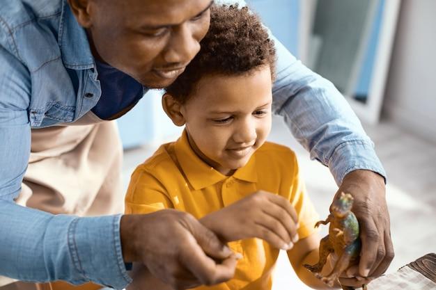 Przyjemna rozrywka. przyjemny młody ojciec bawi się z synkiem w kuchni i wspólnie karmi zabawkowego dinozaura