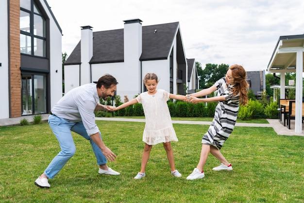 Przyjemna śliczna dziewczyna stojąca między rodzicami podczas spędzania czasu z rodziną