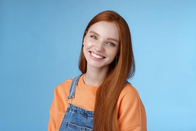 Przyjemna szczera szczęśliwa rudowłosa dziewczyna niebieskie oczy odchylona głowa uśmiechnięty radośnie się śmiać bądź pozytywny szczęśliwy spędzać czas najlepsi przyjaciele otrzymują pochwały dobrą robotę uśmiechnięty zachwycony niebieskie tło