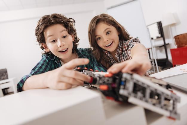 Przyjemna współpraca. pozytywne wesołe wesołe dzieci siedzące w klasie naukowej i używające robota podczas nauki programowania