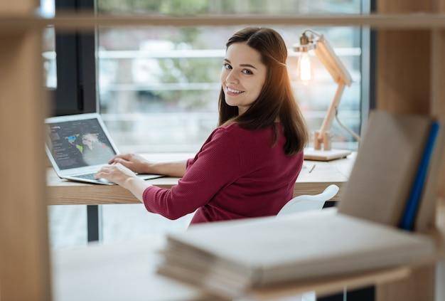 Przyjemne emocje. młoda beztroska kobieta patrzy na ciebie z uśmiechem, siedząc przy stole i używając laptopa
