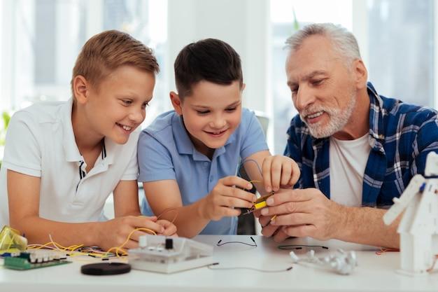 Przyjemne hobby. radosne, inteligentne dzieci siedzą razem z dziadkiem podczas zabawy