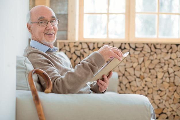 Przyjemne spędzanie czasu. atrakcyjny zadowolony starszy mężczyzna siedzi na kanapie, trzymając książkę i uśmiechając się do kamery