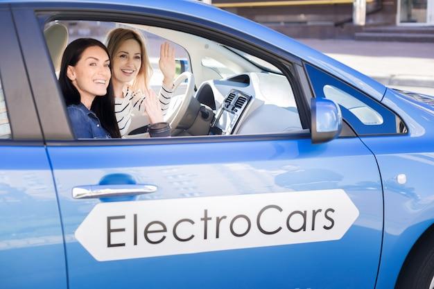 Przyjemne spotkanie. zachwycone szczęśliwe młode kobiety siedzące w samochodzie i machające rękami na spotkanie z przyjaciółką