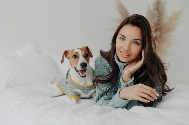 Przyjemnie wyglądająca, czuła kobieta spędza wolny czas z ulubionym zwierzakiem, patrzy bezpośrednio w kamerę