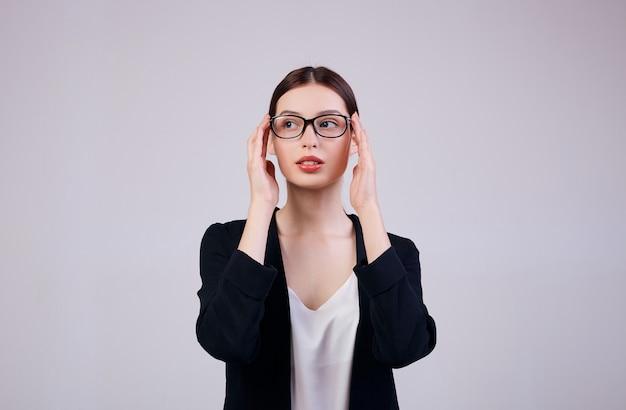 Przyjemnie wyglądająca kobieta biznesu stoi na szaro w czarnej kurtce, białej koszulce i okularach komputerowych. pracownik zajęty.