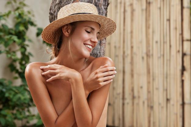 Przyjemnie wyglądająca kobieta pozuje nago, trzyma ręce skrzyżowane, radośnie odwraca wzrok, pozuje samotnie, jest fotografowana dla magazynu. młoda śliczna kobieta o zdrowej skórze i doskonałej figurze uśmiecha się radośnie