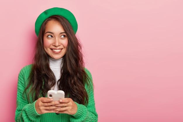 Przyjemnie wyglądająca koreanka ma przemyślany, wesoły wyraz twarzy, nosi zielony sweter i nakrycie głowy, pozuje z telefonem komórkowym