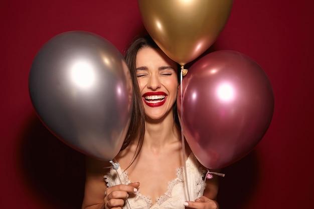 Przyjemnie wyglądająca młoda, bardzo zadowolona, długowłosa brunetka z czerwonymi ustami