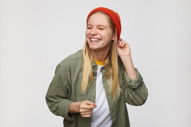 Przyjemnie wyglądająca młoda, dość długowłosa blondynka ubrana w casual, śmiejąca się radośnie z zamkniętymi oczami, stojąc na niebiesko