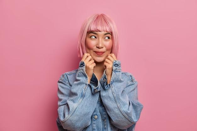 Przyjemnie wyglądająca młoda dziewczyna wygląda z rozmarzonym wyrazem, nosi różową perukę, uśmiecha się radośnie