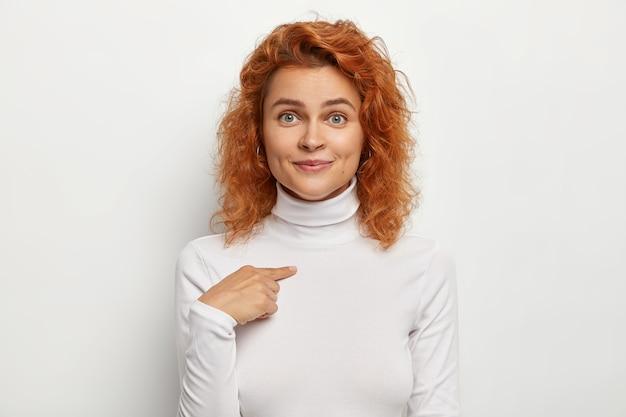 Przyjemnie wyglądająca młoda kobieta wskazuje na siebie, pyta kogo, ma czarujący uśmiech