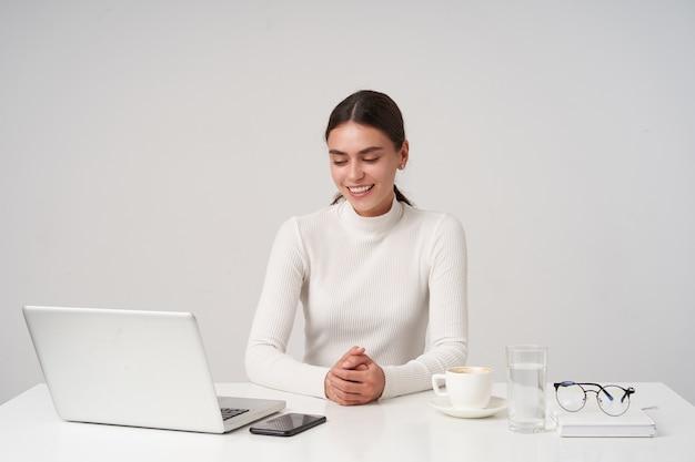Przyjemnie wyglądająca młoda śliczna ciemnowłosa dama z naturalnym makijażem, składająca ręce, siedząca przy stole na białej ścianie i uśmiechająca się pozytywnie, ubrana w formalne ubrania