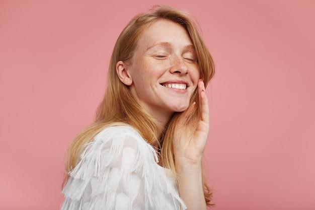 Przyjemnie wyglądająca młoda szczęśliwa dama z lśniącymi włosami trzymająca podniesioną dłoń na policzku i mająca zamknięte oczy, uśmiechając się pozytywnie, ubrana w eleganckie ubrania na różowym tle
