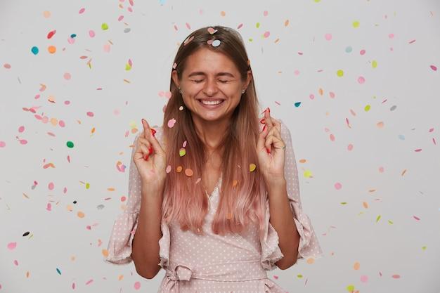 Przyjemnie wyglądająca młoda, szczęśliwa długowłosa blondynka uśmiecha się radośnie, składając życzenia w dniu swoich urodzin i trzymając oczy zamknięte, ubrana w różową romantyczną sukienkę, stojąc na białej ścianie