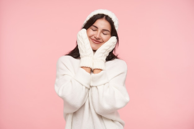 Przyjemnie wyglądająca młoda wesoła brązowowłosa kobieta o swobodnej fryzurze, uśmiechająca się radośnie z zamkniętymi oczami i trzymająca dłonie na policzkach, odizolowana na różowej ścianie