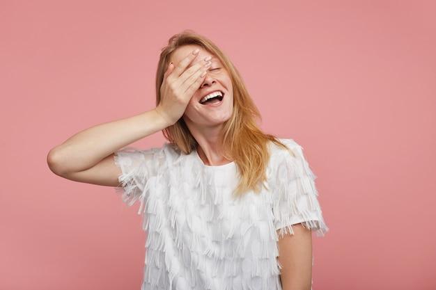 Przyjemnie wyglądająca pozytywnie urocza młoda ruda kobieta trzymająca dłoń na twarzy, uśmiechnięta szczerze, z zamkniętymi oczami podczas pozowania na różowym tle