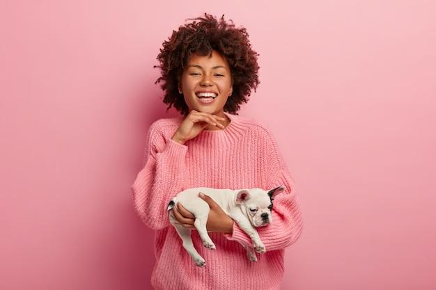 Przyjemnie wyglądająca suczka z zębatym uśmiechem, trzyma podbródek, nosi sennego rodowodowego szczeniaka