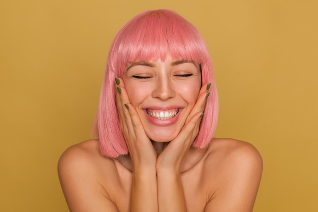 Przyjemnie wyglądająca szczęśliwa młoda dama z krótkimi różowymi włosami trzymająca twarz z uniesionymi dłońmi, pozująca nad musztardową ścianą, z zamkniętymi oczami i szerokim uśmiechem