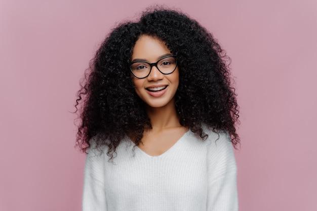 Przyjemnie wyglądająca uśmiechnięta kobieta z fryzurą afro, nosi okulary optyczne i biały sweter