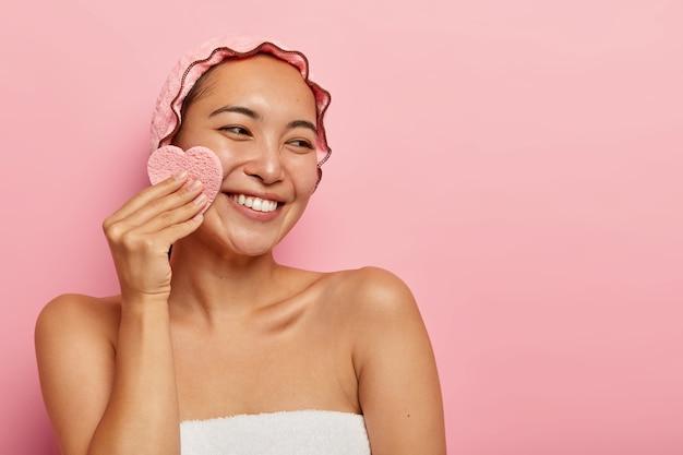 Przyjemnie wyglądająca wesoła azjatka wyciera twarz gąbką kosmetyczną, usuwa makijaż, patrzy na prawą stronę, nosi wodoodporne nakrycie głowy, ma delikatny uśmiech, białe zęby