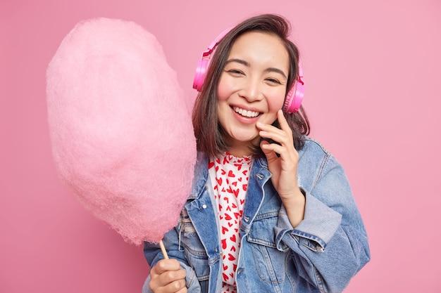 Przyjemnie wyglądająca, wesoła młoda azjatka nosi słuchawki, uśmiecha się z radością, jedząc słodki deser, trzyma pyszną słodką watę cukrową słucha muzyki bawi się na tle różowej ściany