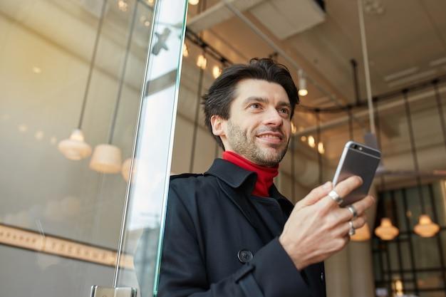 Przyjemnie wyglądający młody atrakcyjny ciemnowłosy mężczyzna uśmiecha się radośnie, trzymając smartfon w uniesionej ręce, pozując nad wnętrzem kawiarni w eleganckich ubraniach