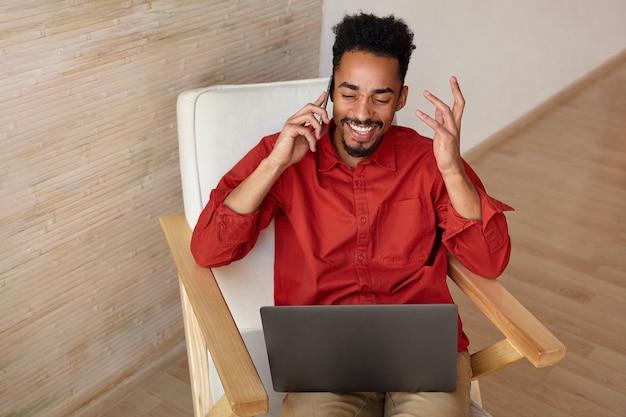 Przyjemnie wyglądający młody brodaty brunet o ciemnej skórze trzymający telefon komórkowy w uniesionej ręce, prowadzący rozmowę telefoniczną i radośnie śmiejący się z zamkniętymi oczami