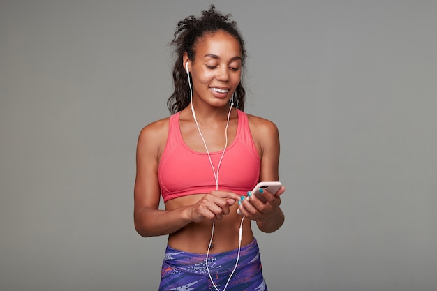 Przyjemnie wyglądający, młody, ciemnoskóry model fitness z kręconymi włosami i swobodną fryzurą, słuchający utworu muzycznego ze słuchawkami i telefonem komórkowym w pozycji stojącej