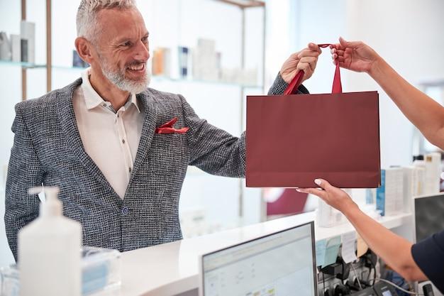 Przyjemnie wyglądający starszy dżentelmen uśmiechający się, gdy odbiera czerwoną torbę z prezentami od recepcjonistki
