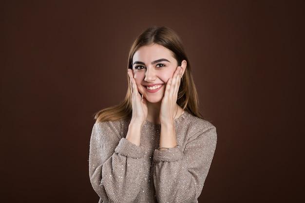 Przyjemnie zdziwiona kobieta spoglądająca spuchniętymi oczami, trzymająca dłonie na policzkach, otwierająca usta ze zdumienia, nie oczekująca tak wspaniałego prezentu. szczęśliwy model odizolowywający nad brąz ścianą