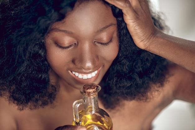 Przyjemność. ciemnoskóra uśmiechnięta kobieta z opadającymi powiekami i zapachem testowania czarnych kręconych włosów cieszy się entuzjastycznie