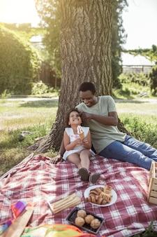 Przyjemność. ciemnoskóry uroczy dzieciak siedzi pod drzewem z tatą i je lody