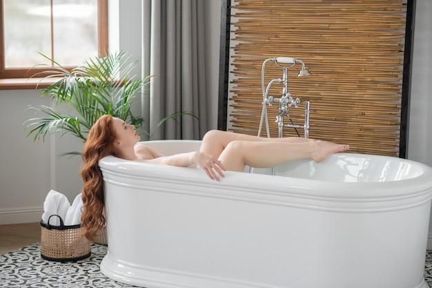 Przyjemność. piękna ruda kobieta leżąca w wannie i wyglądająca na zadowoloną