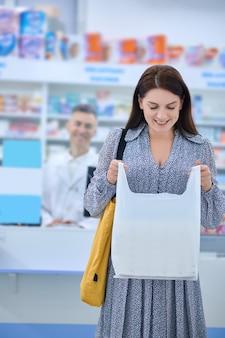 Przyjemność. uśmiechnięta kobieta w sukience patrząca z przyjemnością na paczkę z zakupem w aptece i mężczyzna w białym fartuchu w pobliżu kasy