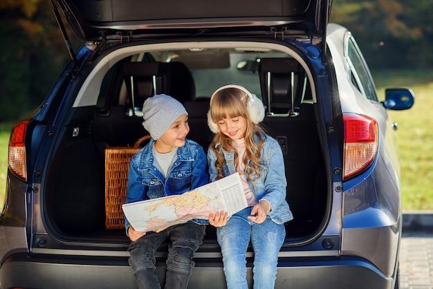 Przyjemny chłopak i dziewczyna patrzą na mapę drogową, siedząc w bagażniku samochodu i omawiając kierunek ruchu. rodzinne wakacje samochodem.