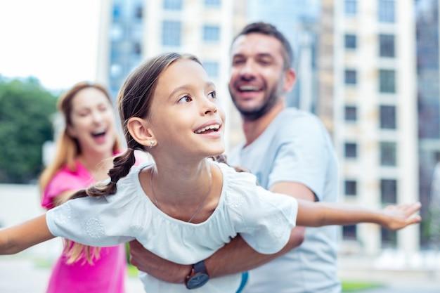 Przyjemny czas. zachwycona szczęśliwa dziewczyna uśmiechając się podczas zabawy z rodzicami
