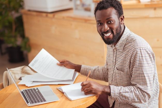 Przyjemny dzień pracy. uroczy młody mężczyzna siedzi w kawiarni, pracuje z danymi w dokumentach i uśmiecha się radośnie do kamery